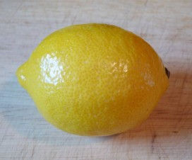 One medium lemon on cutting board.