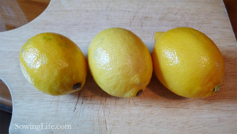 Three medium lemons on cutting board.